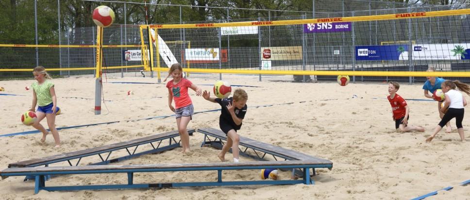 Spelend leren volleyballen in rulle zand