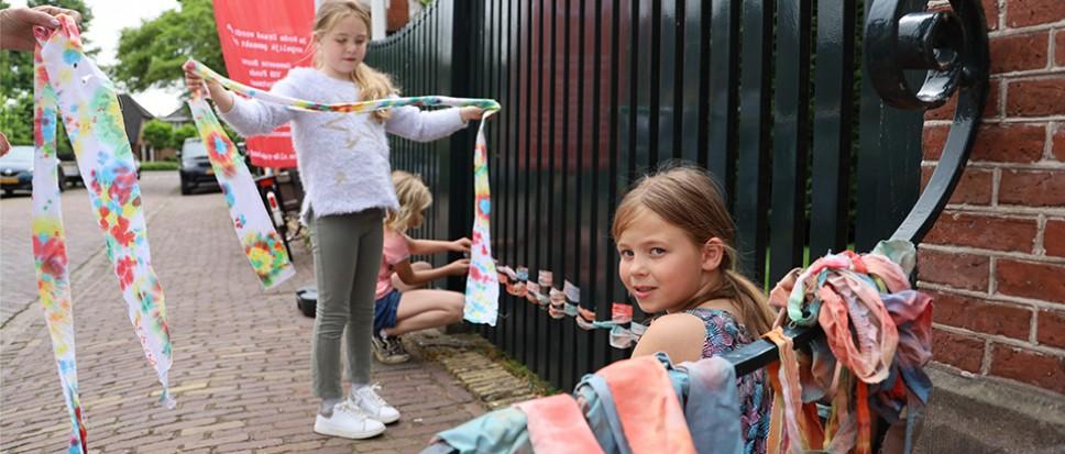 Kinderen gebruiken hek als weefraam