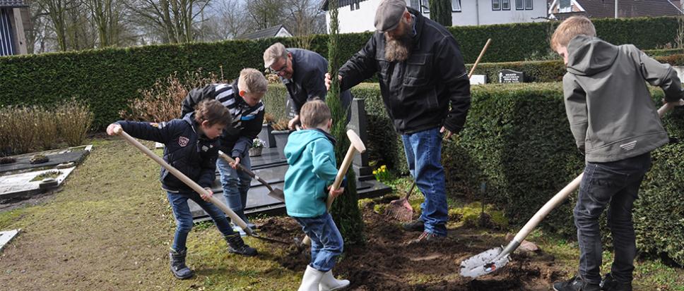 Kinderen planten coniferen op begraafplaats